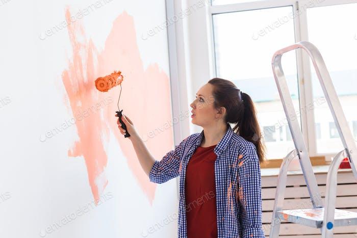Концепция ремонта, ремонта и ремонта - Веселая женщина раскрашивает стену в новом доме