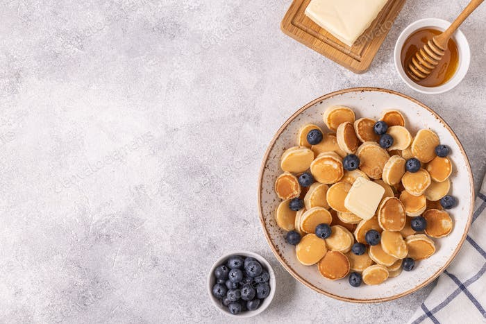 Trendy breakfast with mini pancakes and blueberries.