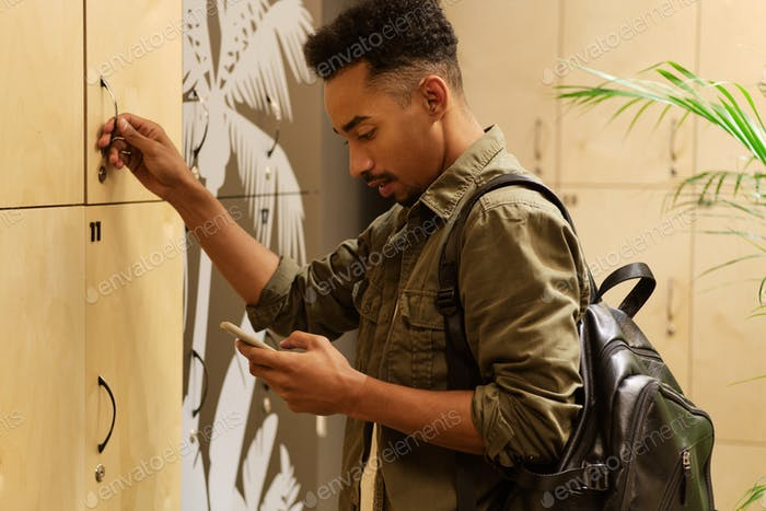 Young attractive casual African American guy thoughtfully using cellphone in locker room
