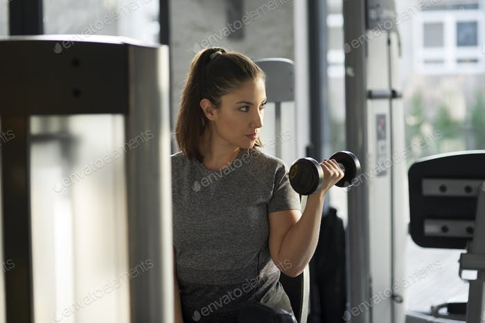 Young woman practicing with dumbbell at the gym