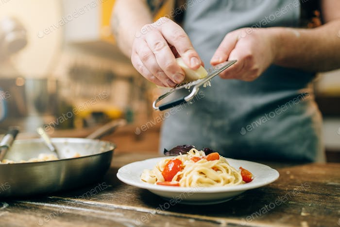 Chef grates cheese to the plate with fresh pasta