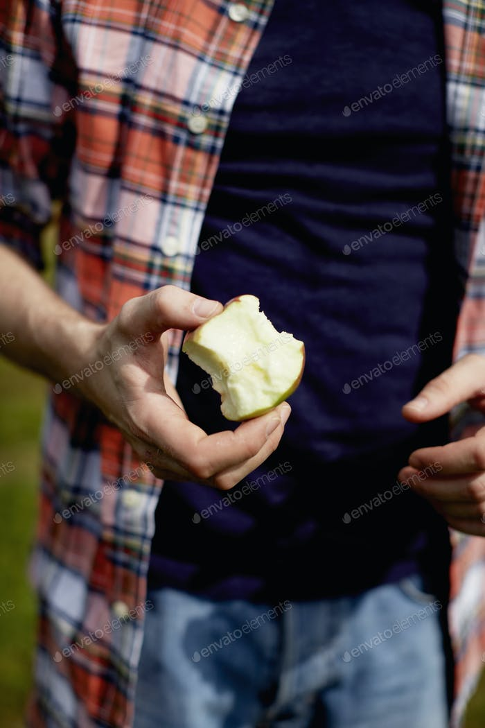 Mid section of a man wearing a plaid shirt, holding a half eaten apple.