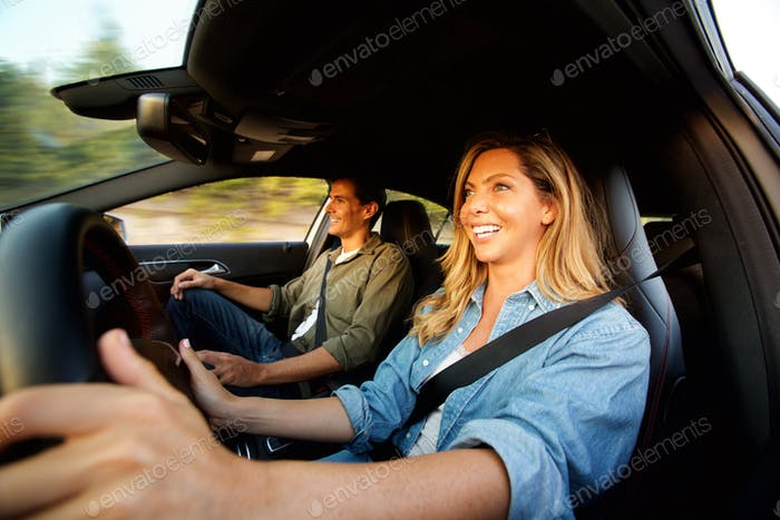 Close up attractive couple laughing in car on road trip