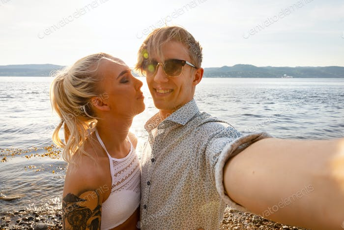 Happy Young Man Taking Selfie With Girlfriend At Beach