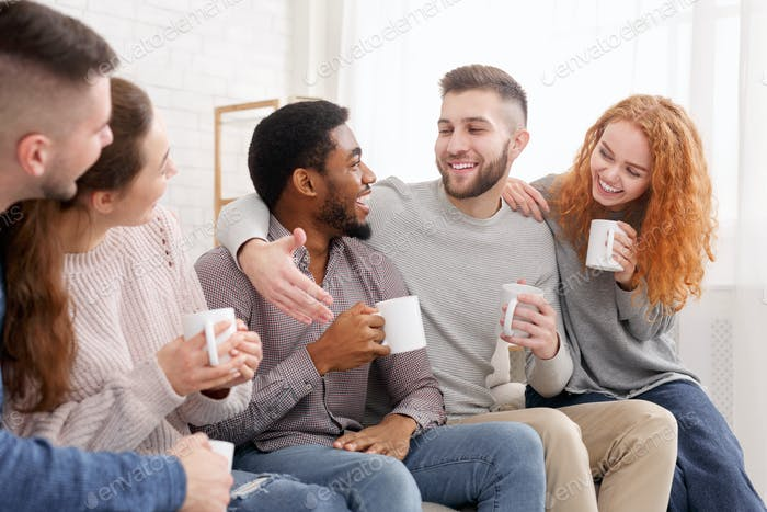 Cheerful friends drinking coffee and enjoying their company