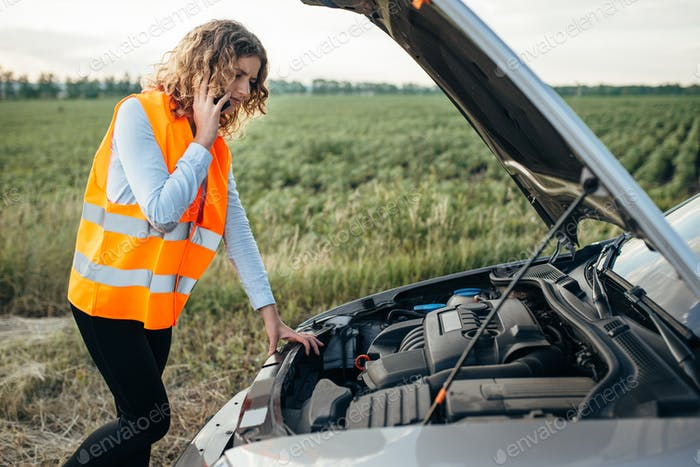 Girl in reflecting vest with phone, broken car