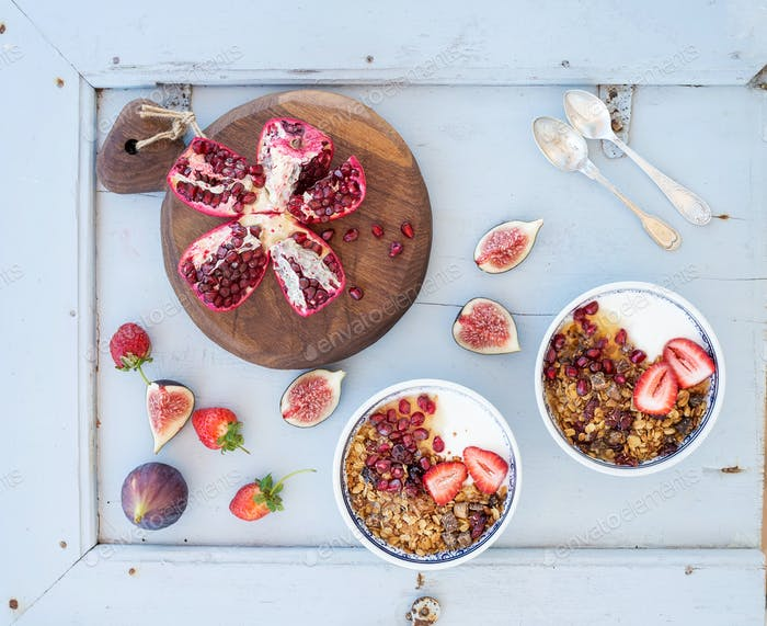 Healthy breakfast set. Bowls of oat granola with yogurt, fresh strawberries