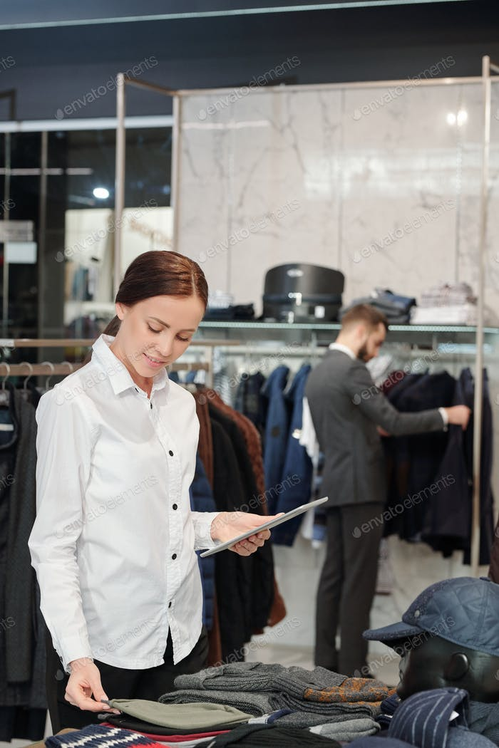 Clothing store employee checking display of garments