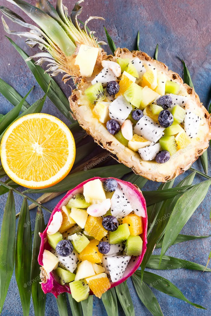 Exotic fruit salad served in half a dragon fruit and pineapple with palm leaf on stone background