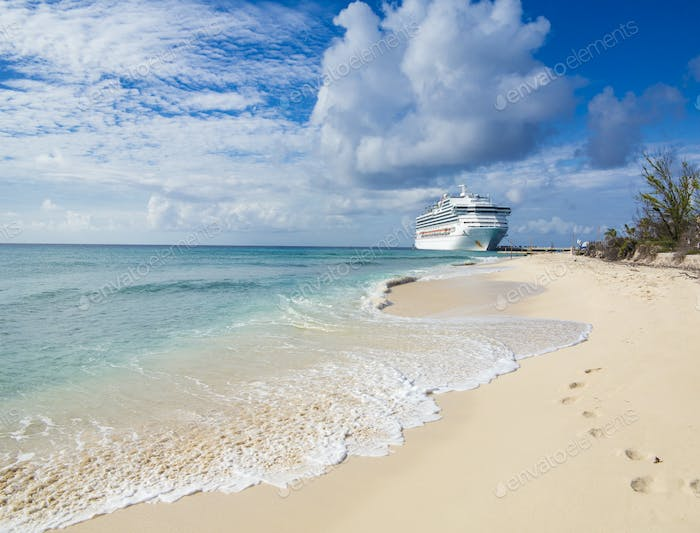 A cruise ship docks in Grand Turk with waves and sand in the for