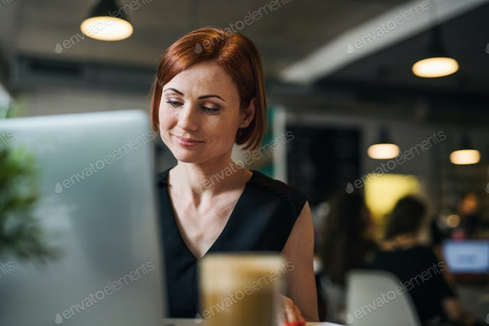 A portrait of woman with coffee sitting at the table in a cafe, using laptop.