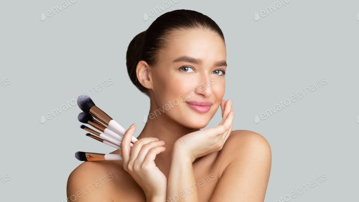 Smiling caucasian young woman holding her makeup brushes