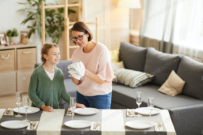 Mother wiping crockery with daughter