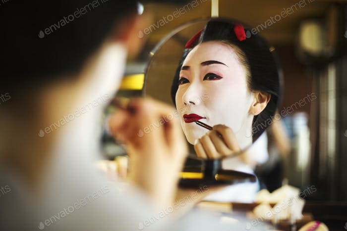 A modern geisha or maiko woman being prepared in traditional fashion, with white face makeup.