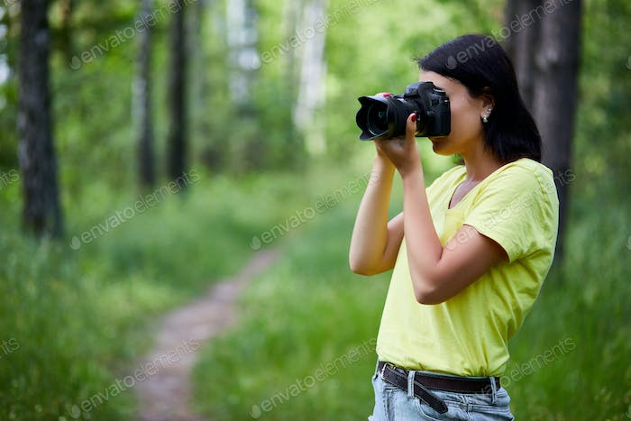 Portrait of a woman photographer covering her face with the camera