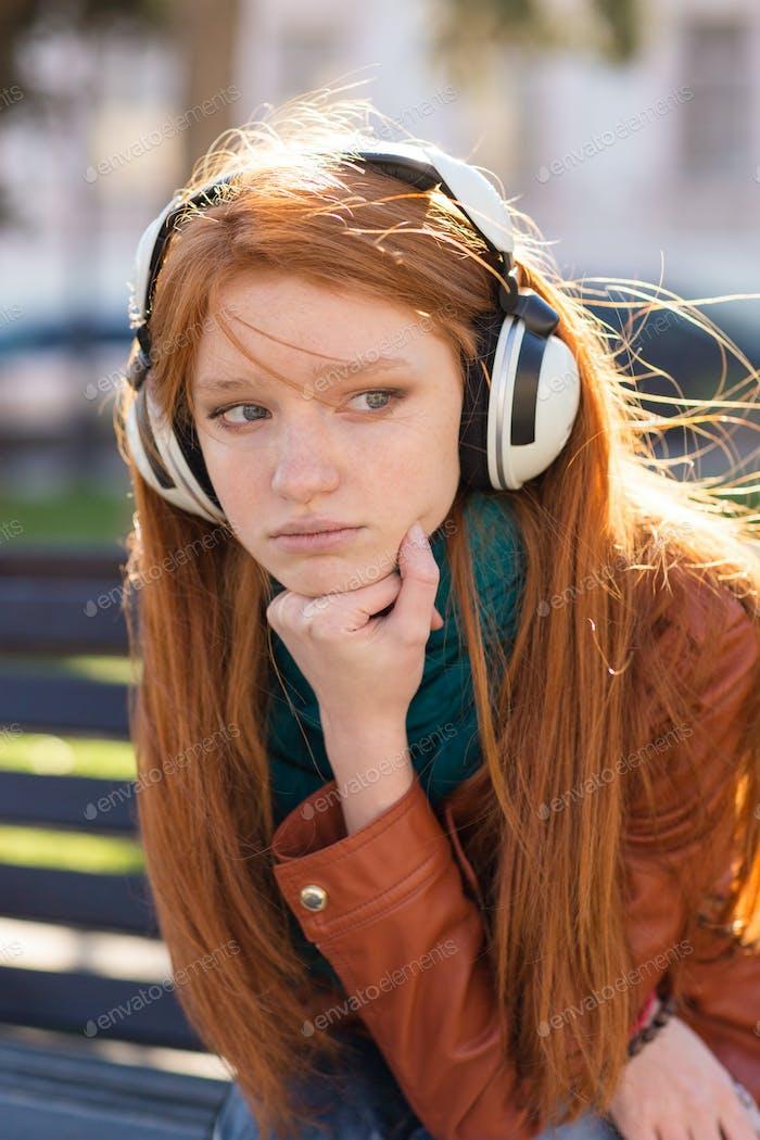 Portrait of beautiful sad pensive young woman in earphones