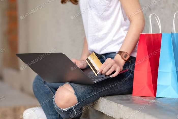 Shopping girl holds credit card in hand.
