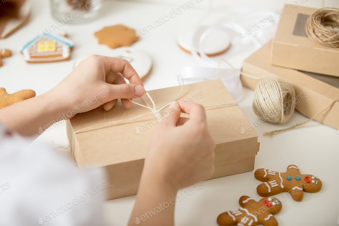 Close up of confectioner hands wrapping a cardboard box