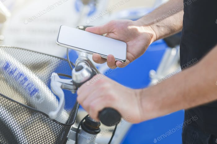 Young cyclist searching GPS coordinates on smartphone