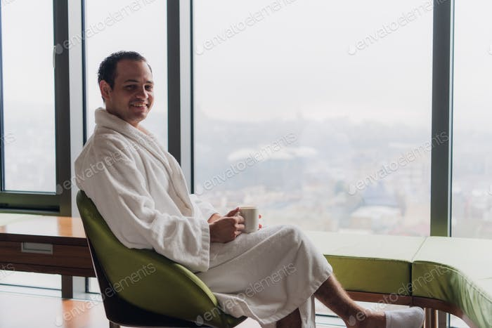 Carefree guy relaxing with hot drink at luxury apartments with great city view