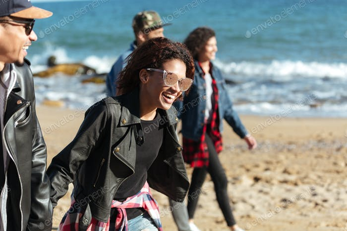 Cheerful african friends walking outdoors at beach.