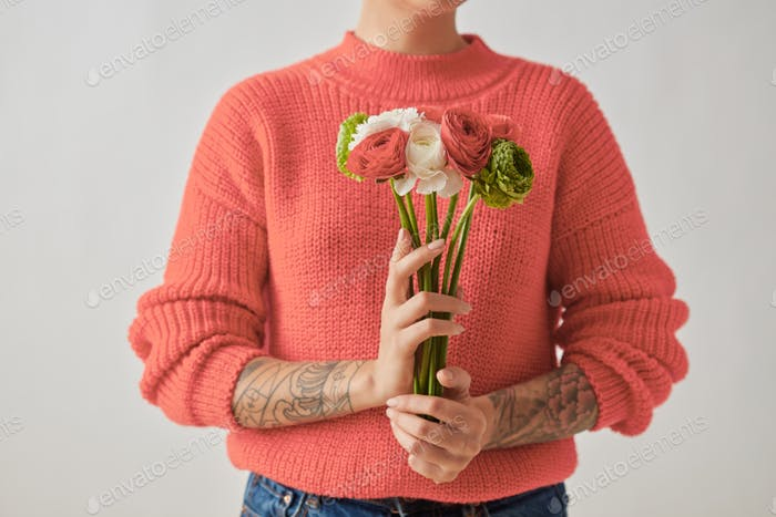 A beautiful bouquet of flowers of a Ranunculus in a girl's hands with tatoo on a gray background