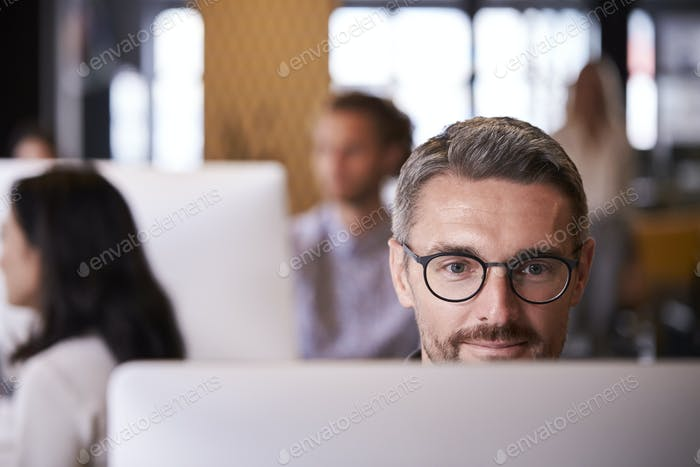 Middle aged white male creative using a computer in a busy office, selective focus, close up