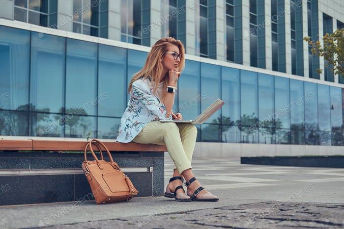 Charming blonde female in modern clothes sitting on a bench in the park against a skyscraper.
