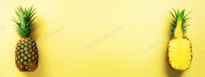 Half slice of fresh pineapple and whole fruit on yellow background. Banner. Top View. Copy Space