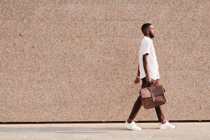 African-American businessman walking with briefcase