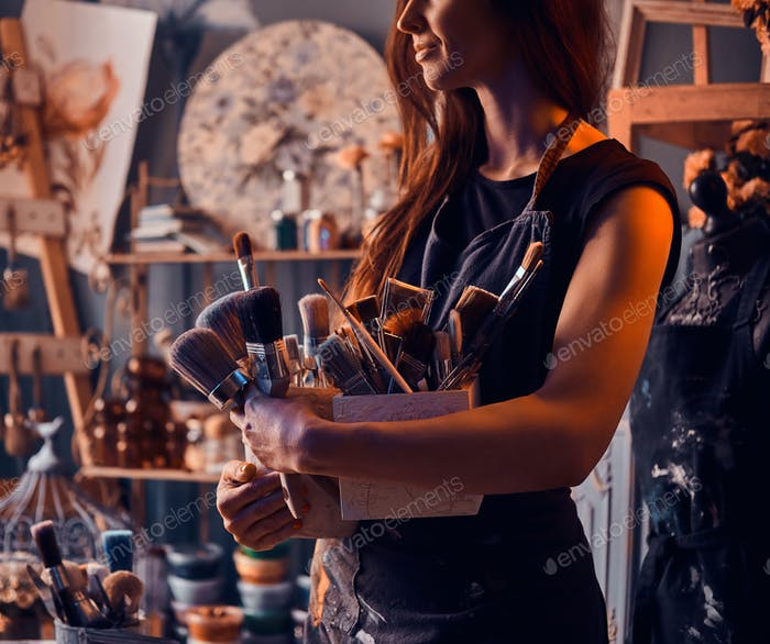 Talented painter is posing with brushes in her own art studio.