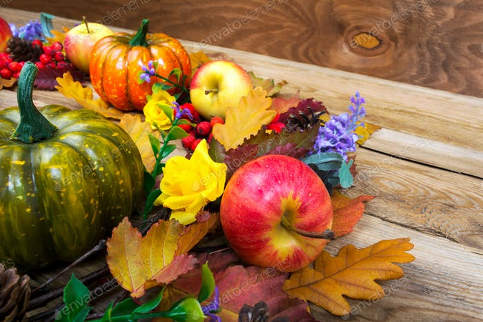 Thanksgiving decor with pumpkins, lilac flowers on the wooden ta