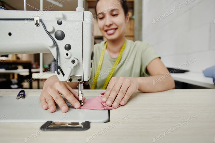 Hands of happy young tailor by electric sewing machine making shoulder pads