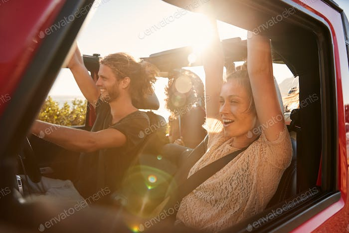 Excited millennial friends on a road trip vacation driving in an open car, close up, lens flare