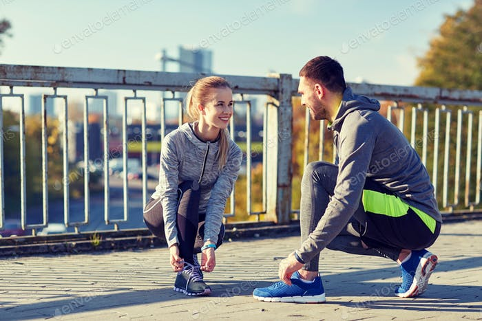 smiling couple tying shoelaces outdoors