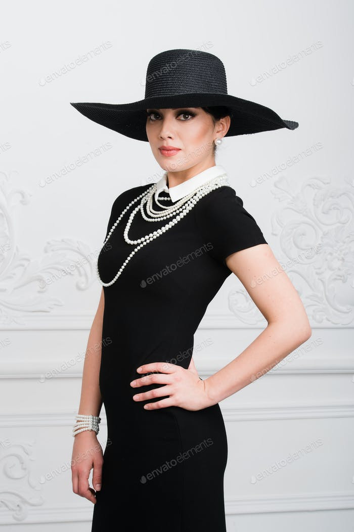 Elegant beautiful young woman in retro style dress, hat standing over light grey background.