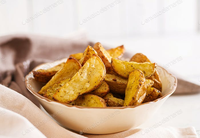 Ruddy Baked potato wedges with garlic on a white background.