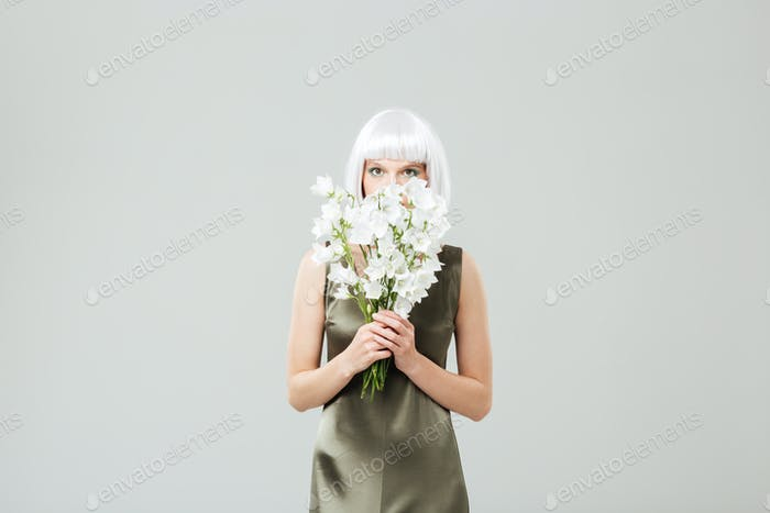 Pretty young woman covered her face with bouquet of flowers