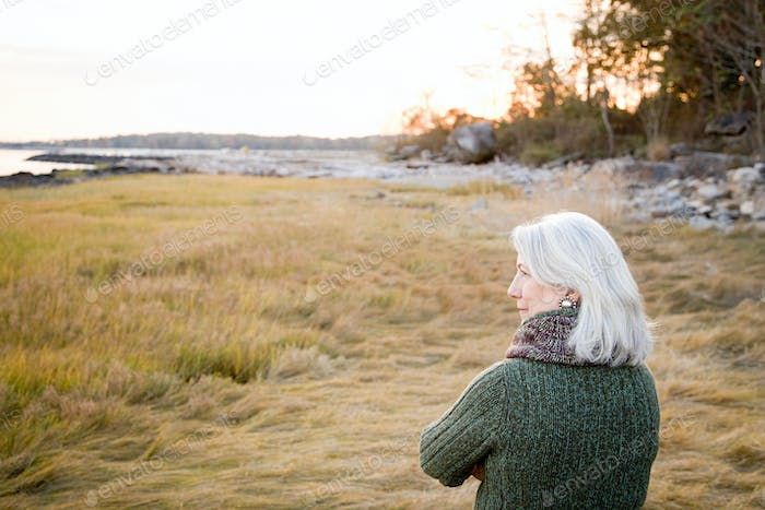 Woman standing on grass near the coast