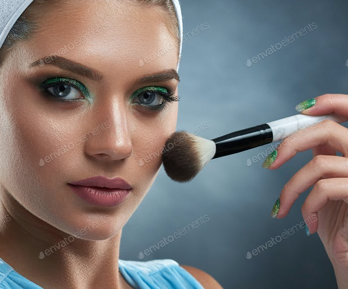 Pretty woman with green makeup drawing blush for herself.