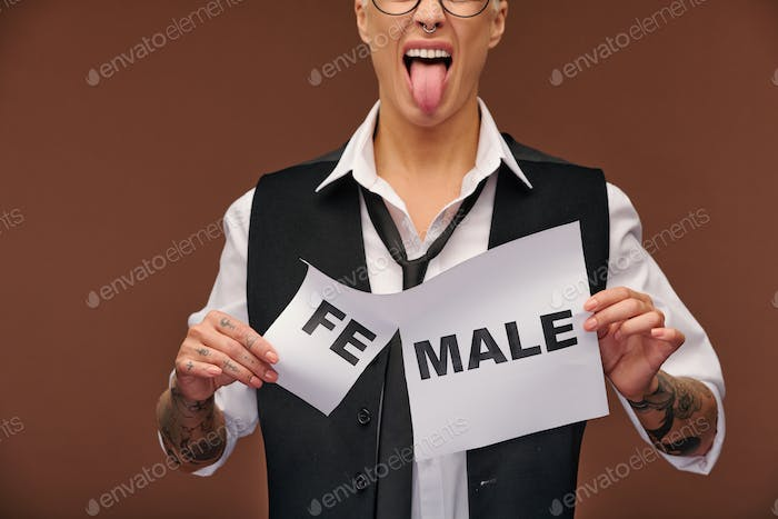 Aggressive young woman in formalwear showing her tongue and tearing paper