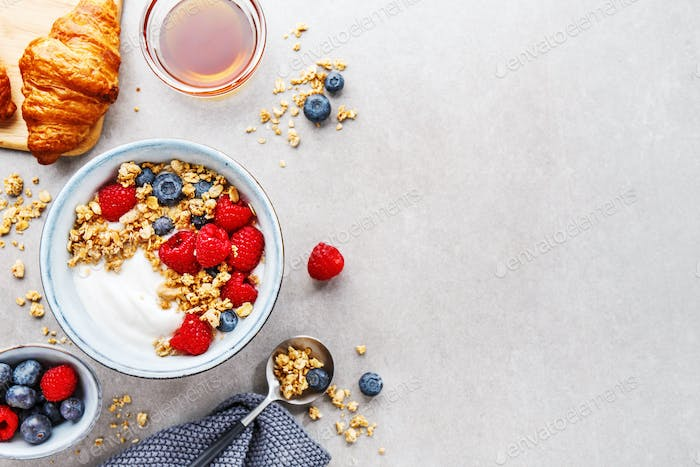 Yogurt with berries and granola in bowl