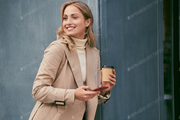 Smiling blond girl in trench coat with coffee to go and cellphone happily looking away outdoor