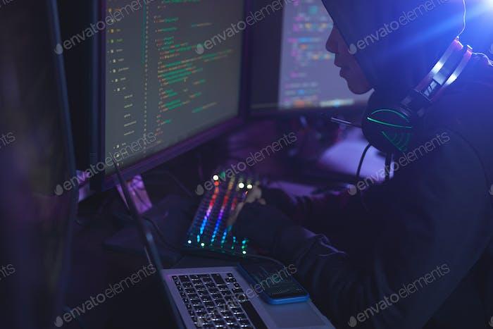 Hooded Man Coding in Dark