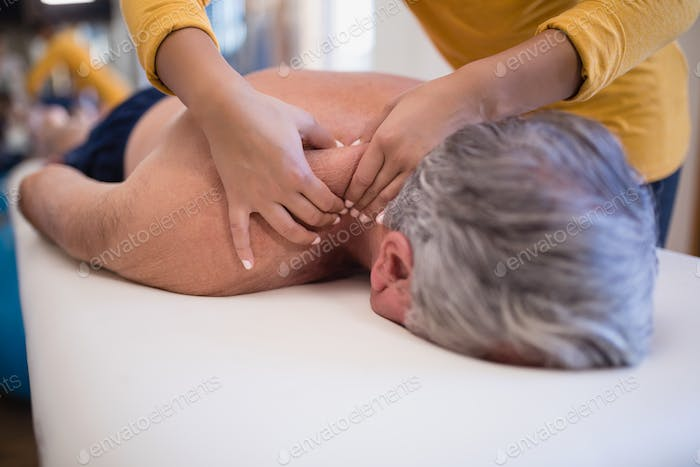Shirtless senior male patient lying on bed receiving neck massage from female therapist
