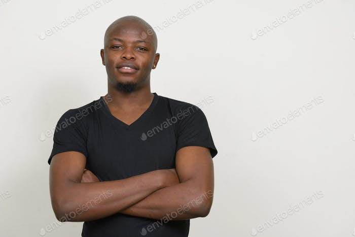 Happy young handsome bald African man smiling with arms crossed
