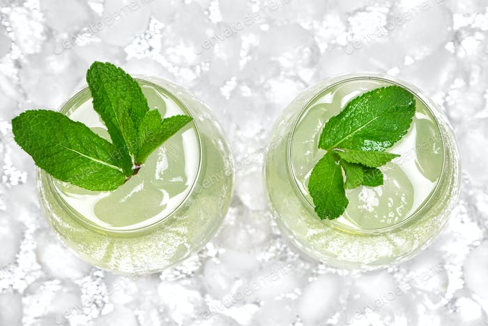 Refreshing drink with mint and ice cubes in large wine glasses