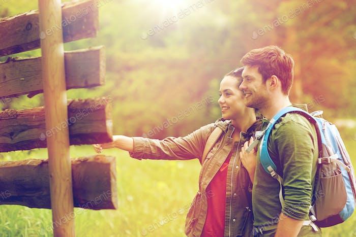lächelnd paar am Wegweiser mit Rucksäcken Wandern