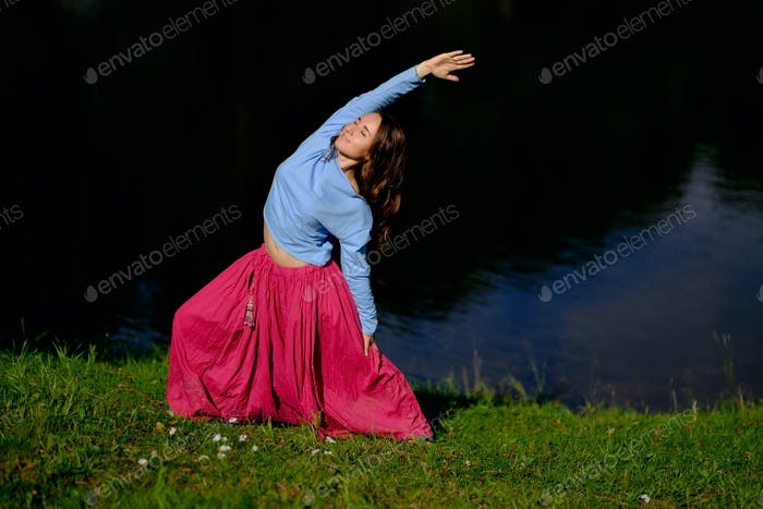 Sporty fit caucasian woman doing asana Virabhadrasana 2 Warrior pose posture in nature.