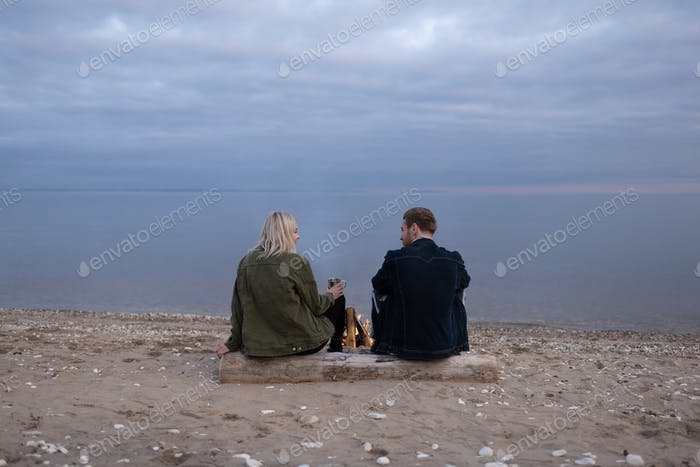 Young couple with tea resting on lake shore